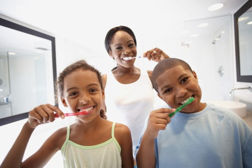 African American mother and children brushing teeth : Stock Photo