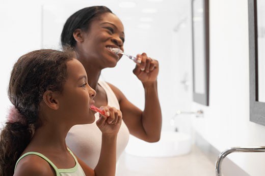 Stock Photo: 1589R-47336 African American mother and daughter brushing teeth
