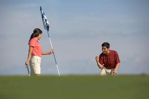 Hispanic couple playing golf : Stock Photo