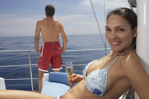 Multi-ethnic couple on sailboat : Stock Photo