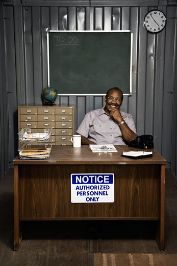 Senior African American male worker sitting at desk : Stock Photo