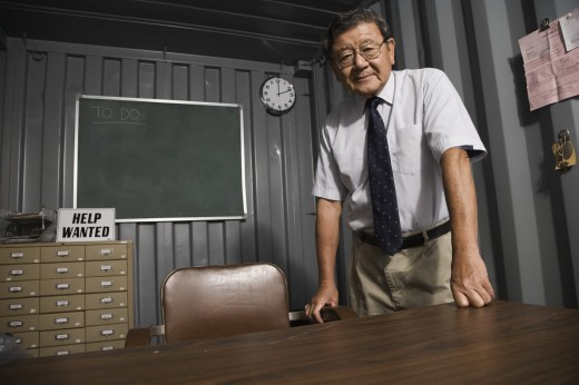 Stock Photo: 1589R-47829 Senior Asian businessman leaning on desk