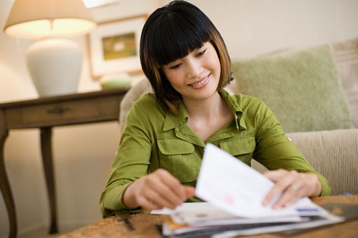 Stock Photo: 1589R-47844 Asian woman looking through mail