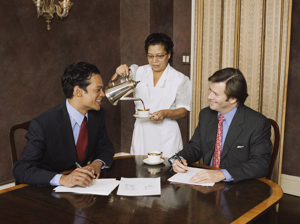 Stock Photo: 1589R-48205 Hispanic maid pouring coffee for businessmen