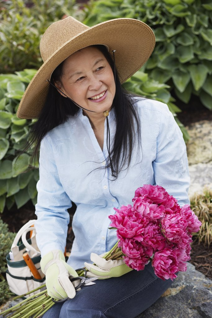 Stock Photo: 1589R-48210 Senior Asian woman holding flowers