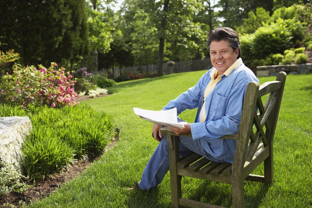 Stock Photo: 1589R-48221 Hispanic man reading in backyard