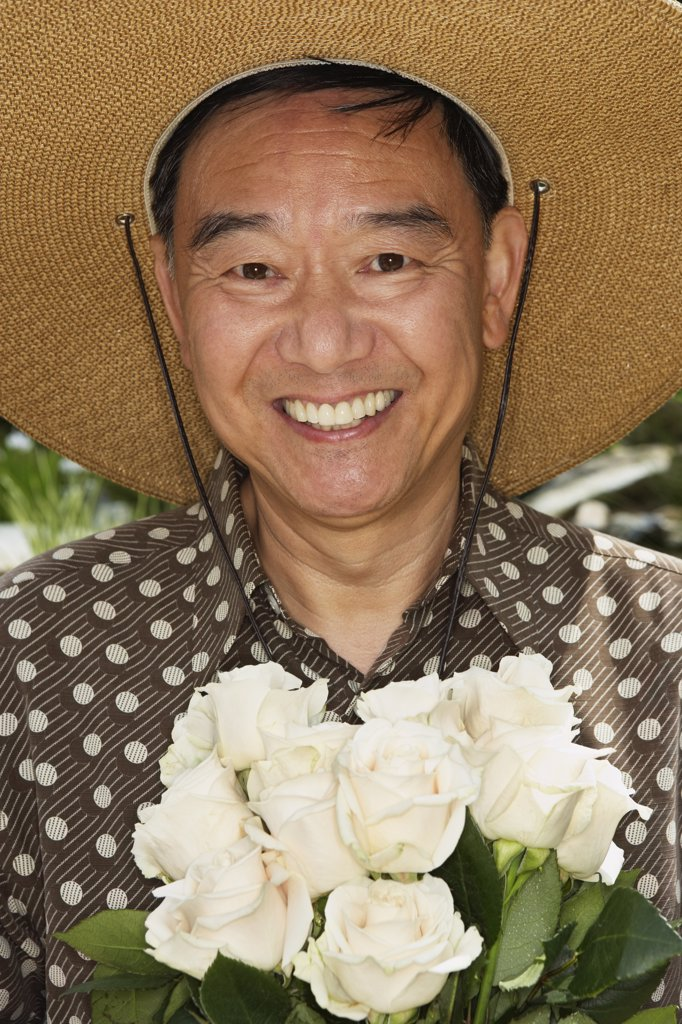 Stock Photo: 1589R-48229 Senior Asian man holding flowers