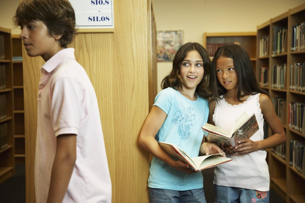 Multi-ethnic girls looking at boy in library : Stock Photo