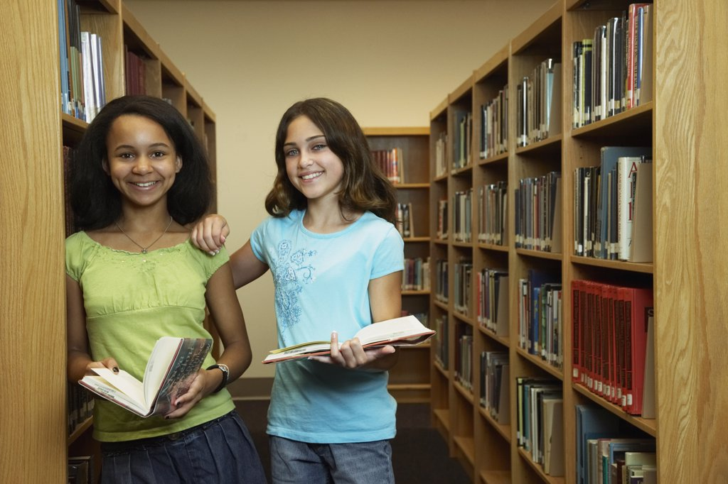 Multi-ethnic girls holding library books : Stock Photo