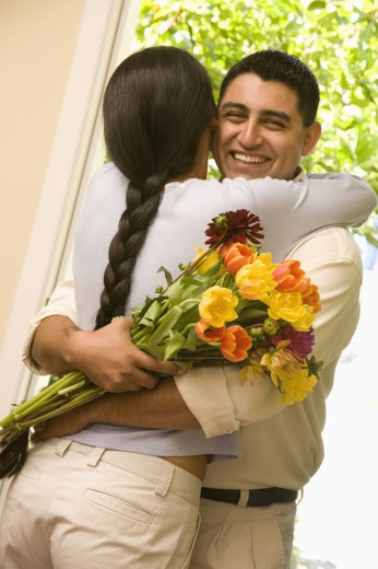 Stock Photo: 1589R-48460 Hispanic couple hugging with flowers