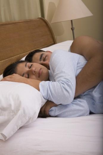 Stock Photo: 1589R-48464 Multi-ethnic couple sleeping in bed