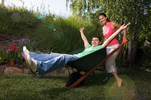 Mixed Race woman pushing boyfriend in wheelbarrow : Stock Photo