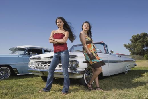 Multi-ethnic women leaning on low rider car : Stock Photo