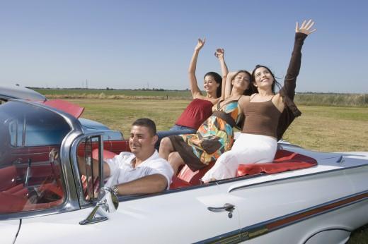 Hispanic man with three women in convertible : Stock Photo
