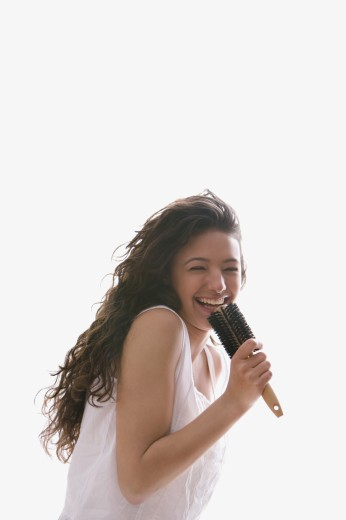 Hispanic teenaged girl singing into hairbrush : Stock Photo