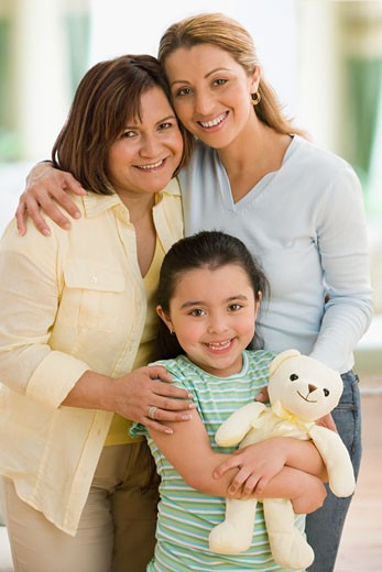 Stock Photo: 1589R-48715 Hispanic grandmother, mother and daughter hugging