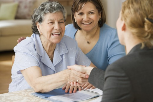 Senior Hispanic woman shaking hands with businesswoman : Stock Photo