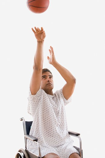 Stock Photo: 1589R-48929 Hispanic man in wheelchair shooting basketball
