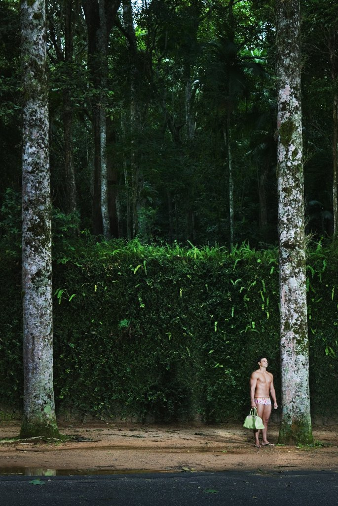Stock Photo: 1589R-49095 Hispanic man wearing bathing suit in woods