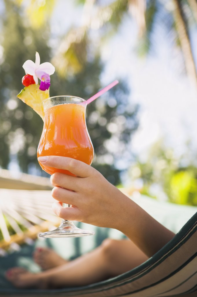 Stock Photo: 1589R-49448 Asian woman with cocktail in hammock