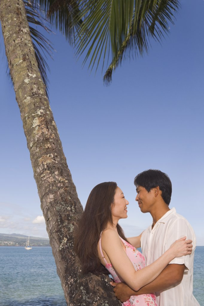 Stock Photo: 1589R-49462 Asian couple hugging at beach
