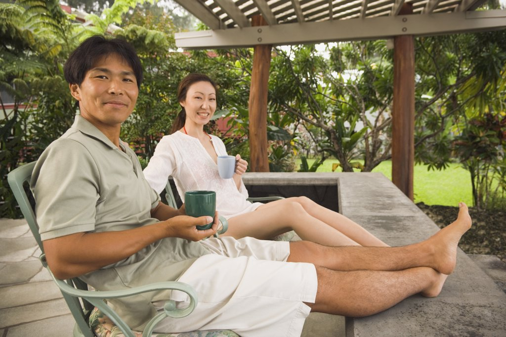 Asian couple on patio with coffee : Stock Photo