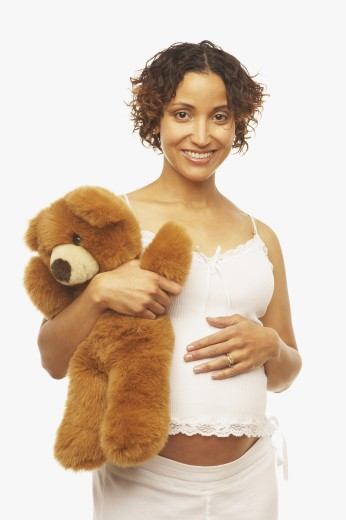 Pregnant Mixed Race woman holding teddy bear : Stock Photo