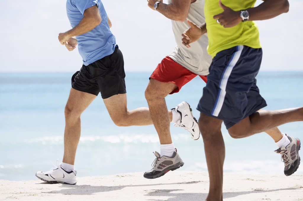 Stock Photo: 1589R-49637 Multi-ethnic men running in beach