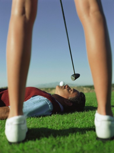 Stock Photo: 1589R-49684 Woman swinging at golf ball in man's mouth