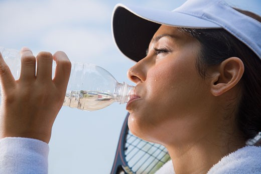 Hispanic woman drinking from water bottle : Stock Photo