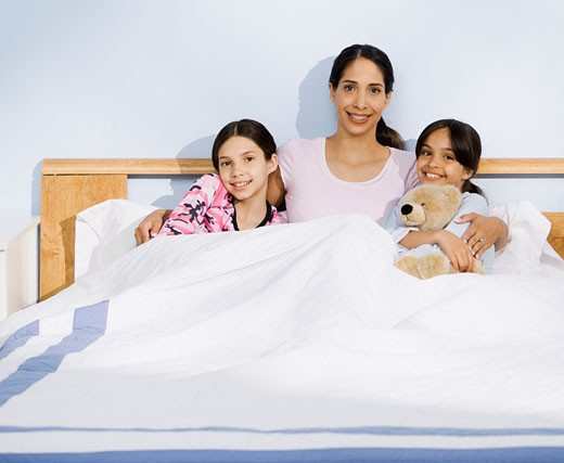 Stock Photo: 1589R-49920 Hispanic mother and daughters sitting in bed