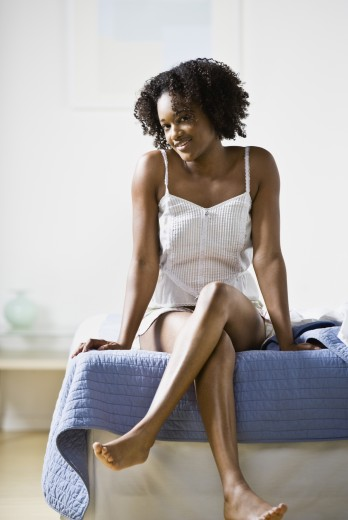 Stock Photo: 1589R-49977 African American woman sitting on edge of bed