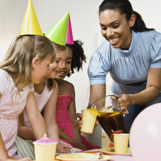 Stock Photo: 1589R-50103 Mixed Race woman pouring drink at daughter's party