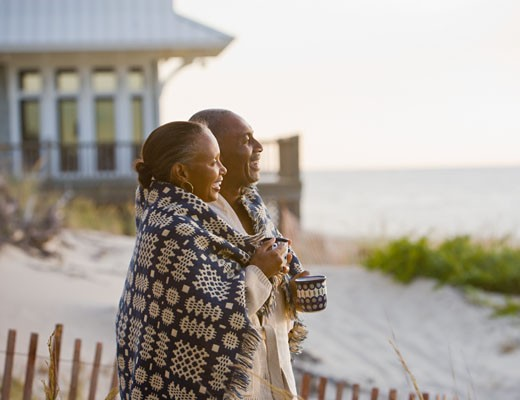 Senior African American couple wrapped in blanket : Stock Photo