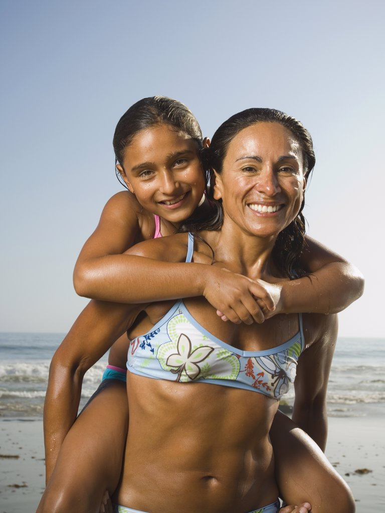 Hispanic mother giving daughter piggyback ride : Stock Photo