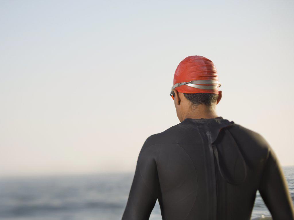 Stock Photo: 1589R-50356 Rear view of Hispanic man wearing wetsuit