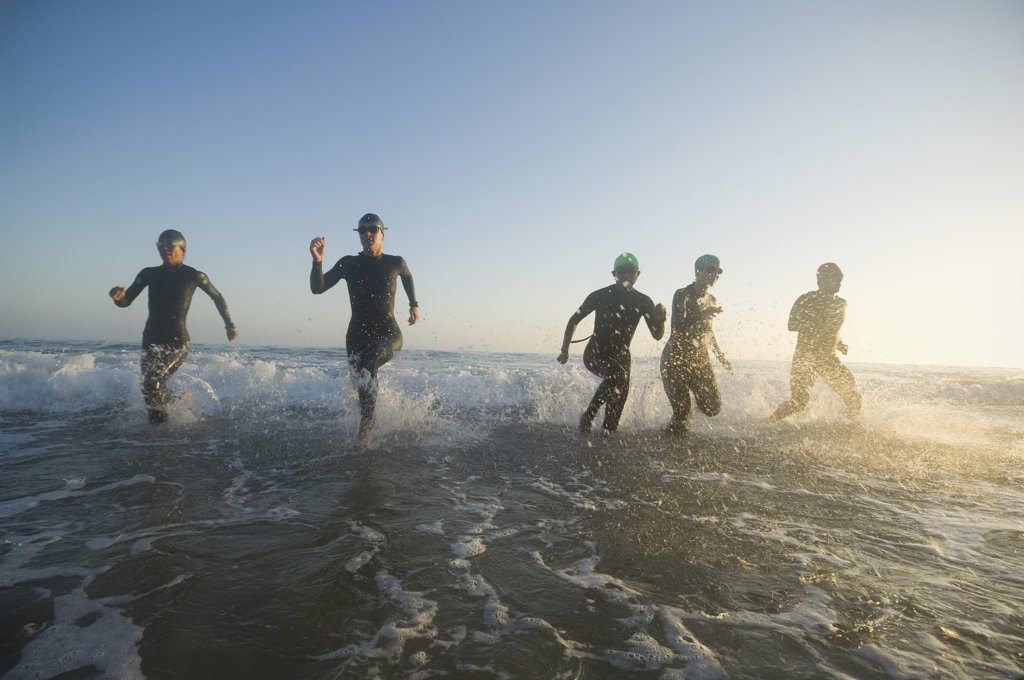 Stock Photo: 1589R-50371 Multi-ethnic swimmers running in surf