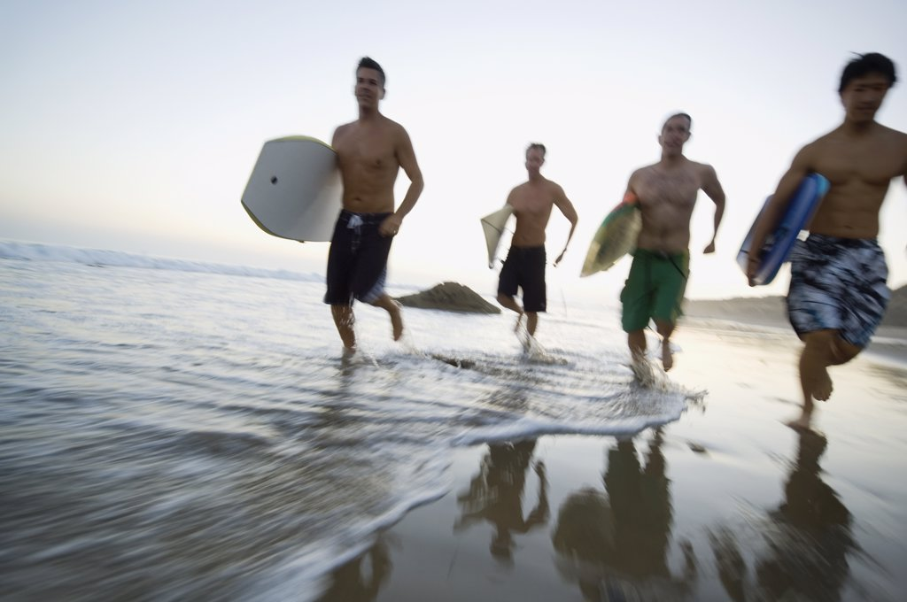 Multi-ethnic men running with surfboards : Stock Photo