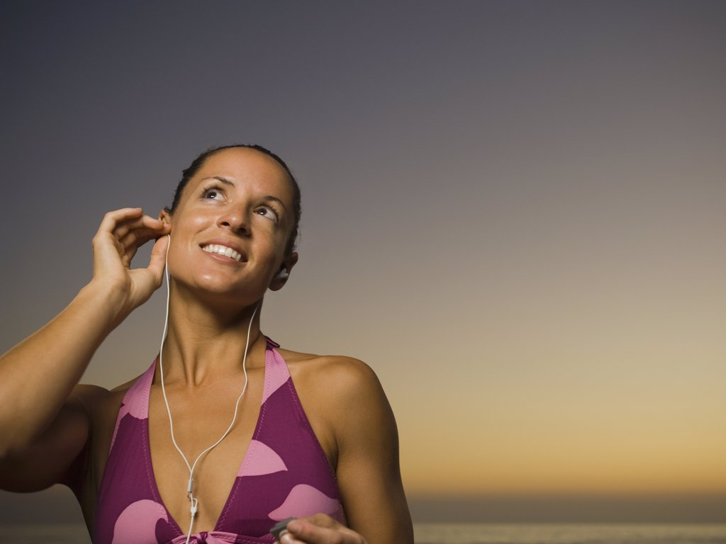 Hispanic woman listening to mp3 player : Stock Photo