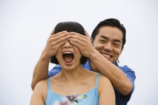 Asian man covering girlfriend's eyes : Stock Photo