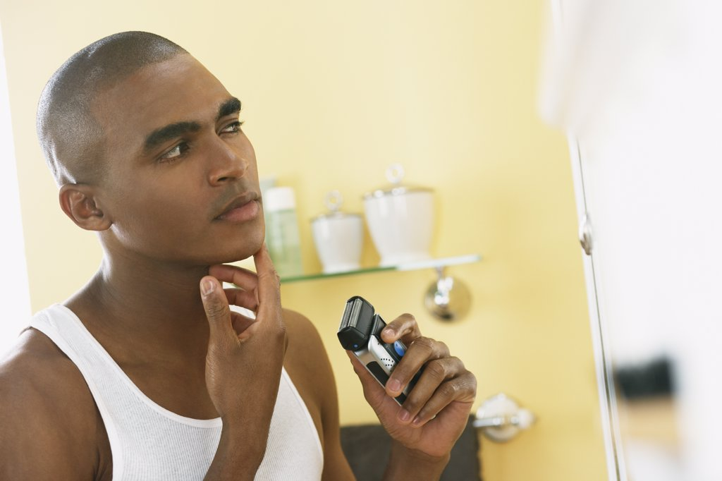 Stock Photo: 1589R-50591 African man shaving with electric razor