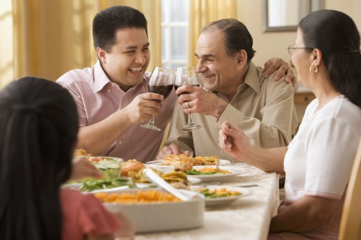 Hispanic father and adult son toasting at dinner table : Stock Photo