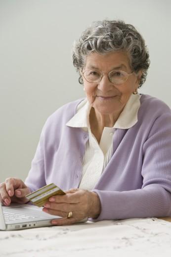 Senior Hispanic woman shopping online : Stock Photo
