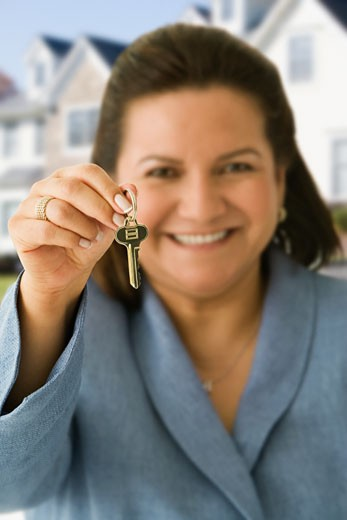 Hispanic woman holding house key : Stock Photo