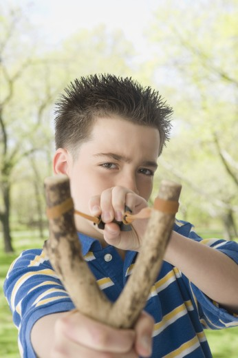 Hispanic boy pulling on sling shot : Stock Photo