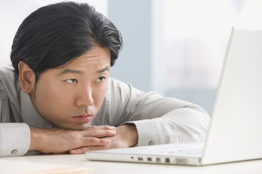 Asian businessman looking at laptop : Stock Photo