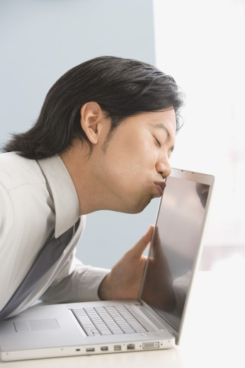Stock Photo: 1589R-51045 Asian businessman kissing laptop