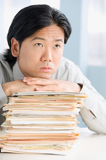 Stock Photo: 1589R-51046 Asian businessman leaning on stack of paperwork