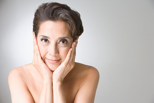 Hispanic woman with hands on face : Stock Photo