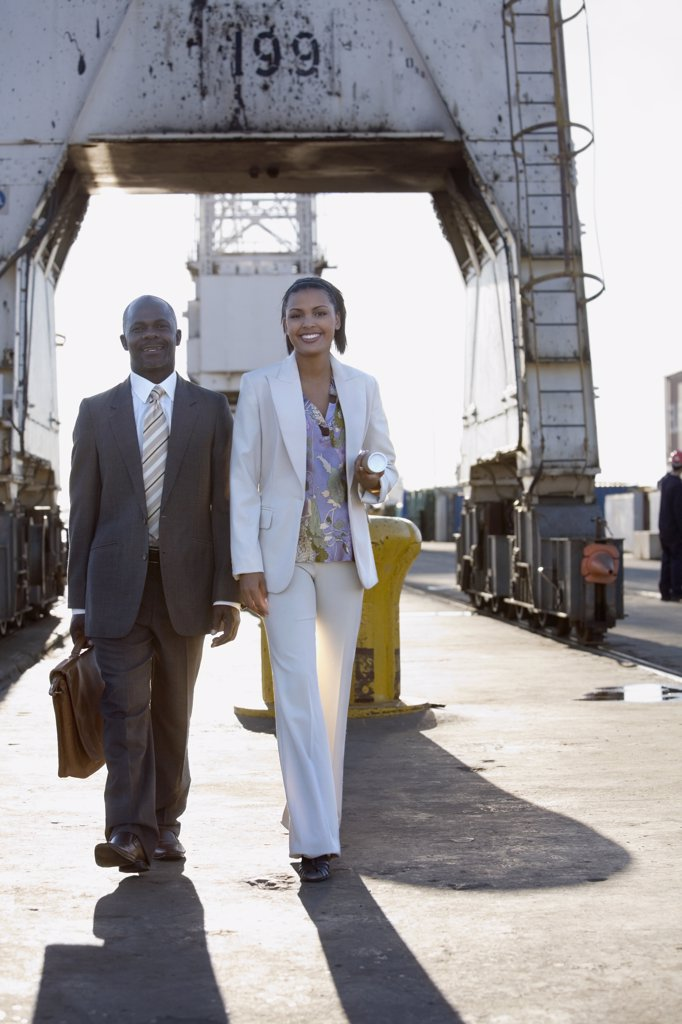 African American businesspeople walking on commercial pier : Stock Photo